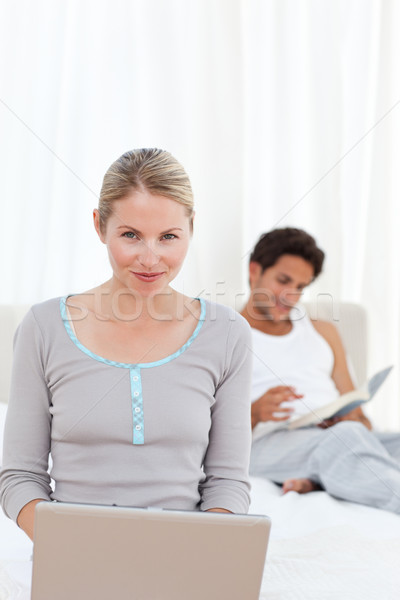 Woman working on her laptop while her husband is reading at home Stock photo © wavebreak_media