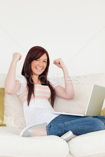 Beautiful red-haired woman being joyful after gambling with her laptop while sitting on a sofa in th Stock photo © wavebreak_media