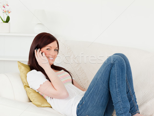 Charming red-haired woman having a conversation on the phone while lying on a sofa in the living roo Stock photo © wavebreak_media