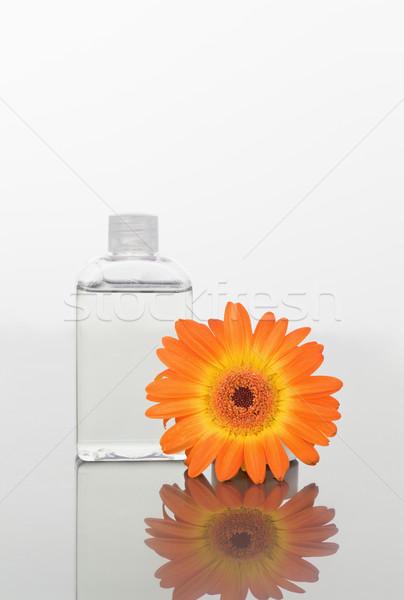 Orange gerbera and a glass flask on a mirror agains white back ground Stock photo © wavebreak_media
