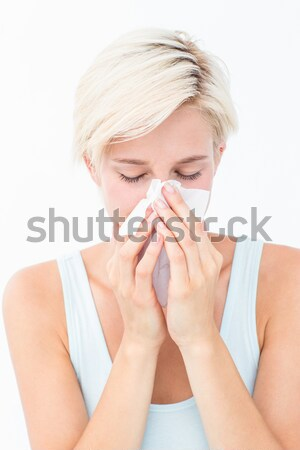Attractive woman sneezing while standing against a white background Stock photo © wavebreak_media