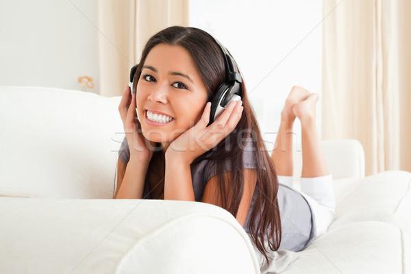 Bájos nő kanapé fülhallgató néz kamera Stock fotó © wavebreak_media