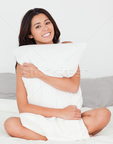Cute femme oreiller séance lit souriant Photo stock © wavebreak_media