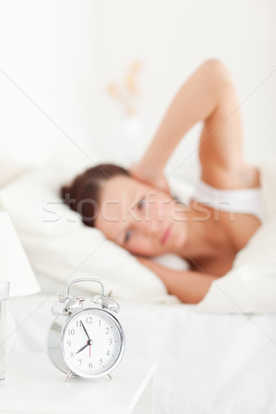 Close up of a good looking red-haired woman lying in bed not wanting to hear the alarm clock Stock photo © wavebreak_media