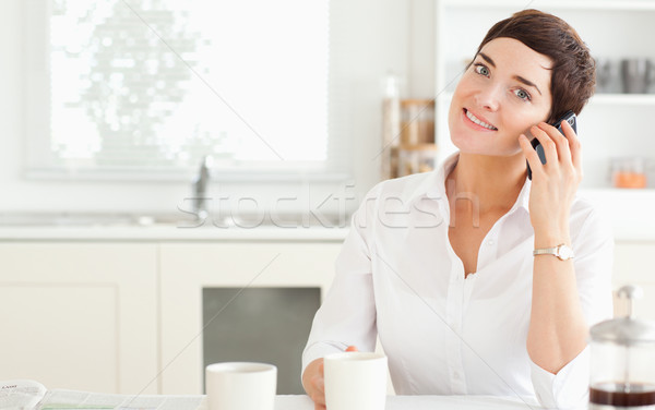 A woman with a coffee telephoning in the kitchen at morning Stock photo © wavebreak_media