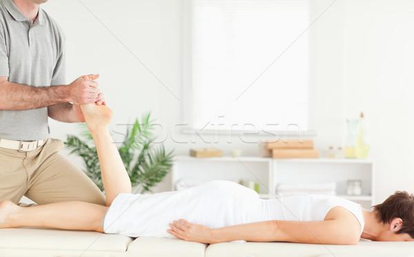 A masseur massages a female customer's leg Stock photo © wavebreak_media