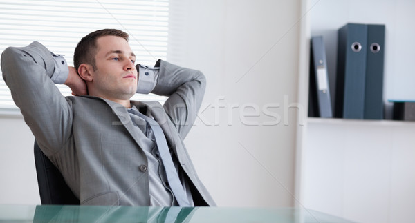 Businessman relaxing sitting behind a table Stock photo © wavebreak_media