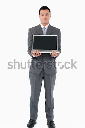 Confident young businessman presenting his notebook against a white background Stock photo © wavebreak_media