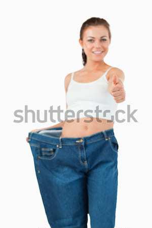 Portrait of a fit woman wearing too large jeans with the thumb up against a white background Stock photo © wavebreak_media