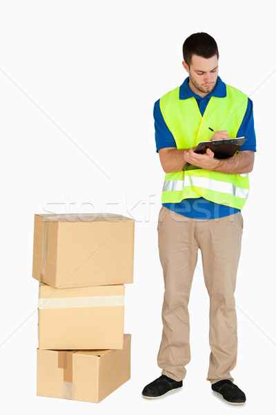 Young delivery man completing delivery note against a white background Stock photo © wavebreak_media