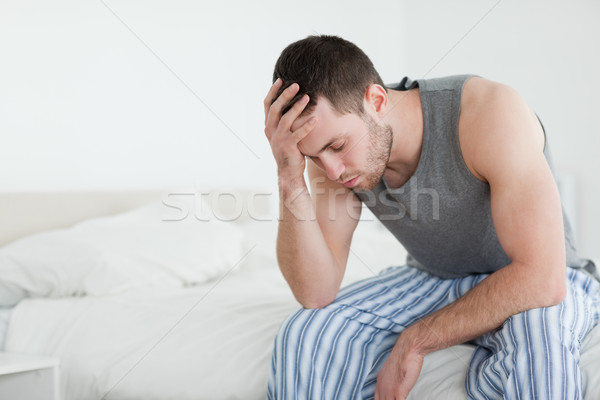 Exhausted man sitting on his bed with his eyes closed Stock photo © wavebreak_media