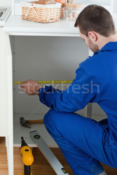 Stock photo: Portrait of a handyman measuring something in a kitchen