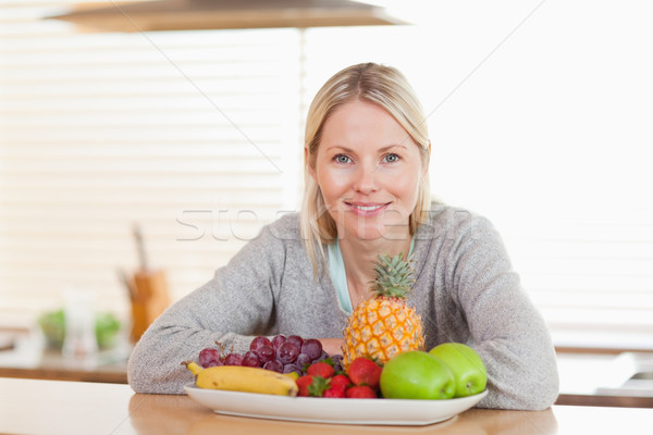 Young woman sitting in the kitchen with a plate of fruits Stock photo © wavebreak_media