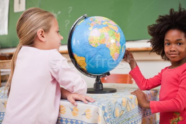 Cute schoolgirls looking at a globe in a classroom Stock photo © wavebreak_media