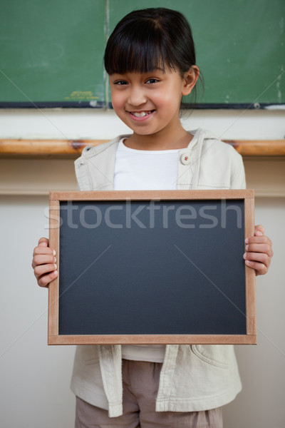 Portrait of a girl holding a school slate in a classroom Stock photo © wavebreak_media