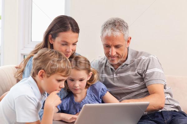 Сток-фото: счастливая · семья · сидят · диван · ноутбук · гостиной · семьи