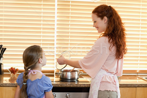 Smiling mother showing her daughter what shes cooking Stock photo © wavebreak_media