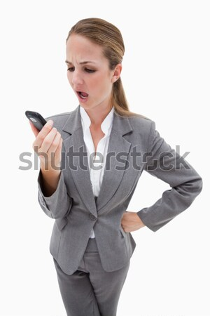 Indignant looking bank employee reading text message against a white background Stock photo © wavebreak_media