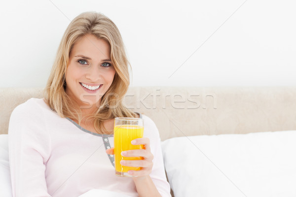 Mulher sessão cama vidro suco de laranja olhando Foto stock © wavebreak_media