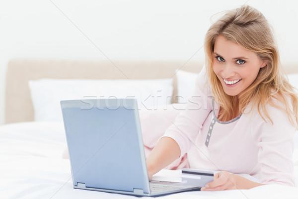 Femme lit souriant regarder vers l'avant portable Photo stock © wavebreak_media