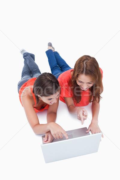 Dos sonriendo adolescentes senalando portátil Screen Foto stock © wavebreak_media