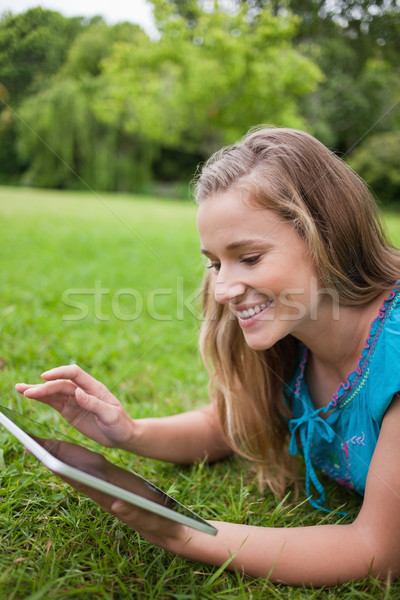 Young happy woman using her tablet pc while lying on the grass in a public garden Stock photo © wavebreak_media