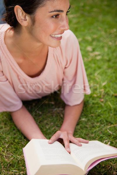 Femme regarder côté lecture livre couché Photo stock © wavebreak_media
