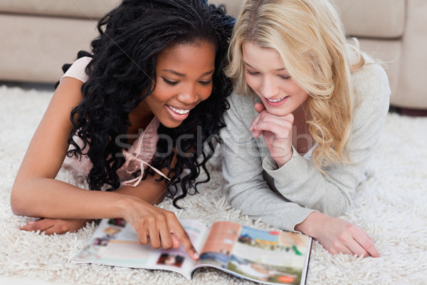A woman lying on the floor is pointing at a magazine with her friend lying beside her Stock photo © wavebreak_media
