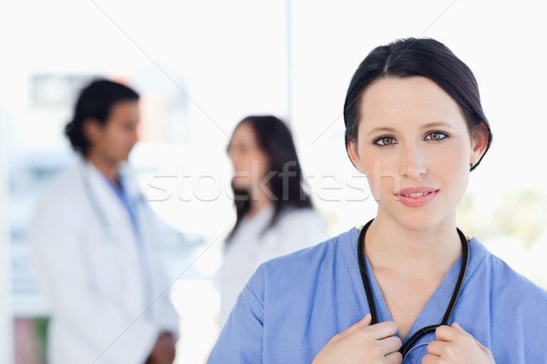 Serious intern looking at the camera while her medical team is in the background Stock photo © wavebreak_media