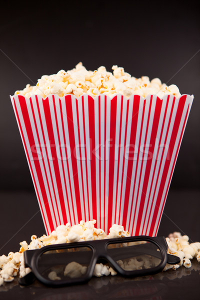 3D glasses on popcorn at the feet of a box of popcorn against a black background Stock photo © wavebreak_media