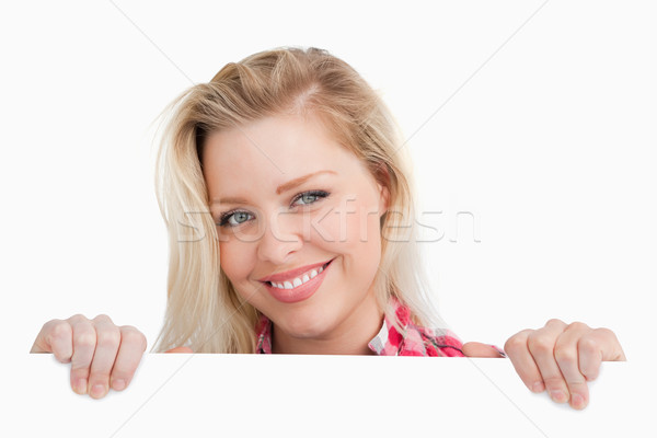 Woman beaming while holding a blank sign against a white background Stock photo © wavebreak_media