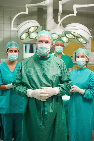 Uśmiechnięty chirurg stwarzające medycznych zespołu chirurgiczny Zdjęcia stock © wavebreak_media