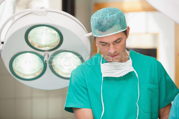 Surgeon standing in the operating room while concentrating Stock photo © wavebreak_media