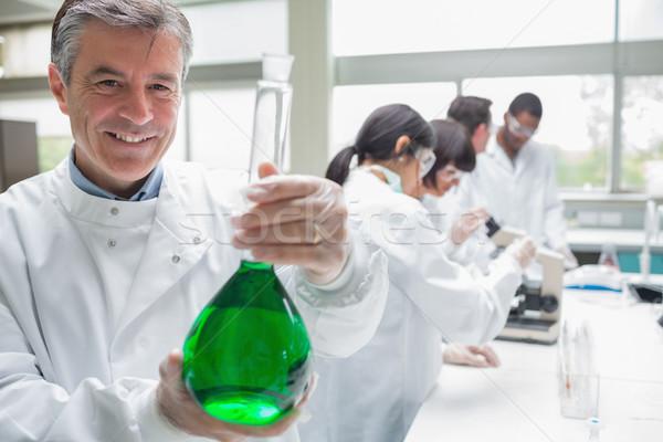 Vegyész mosolyog tart főzőpohár zöld folyadék Stock fotó © wavebreak_media