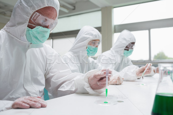 Stock photo: Chemists in protective suits working in the laboratory