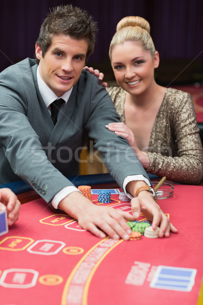 Man happily taking the pot with women beside him in casino Stock photo © wavebreak_media