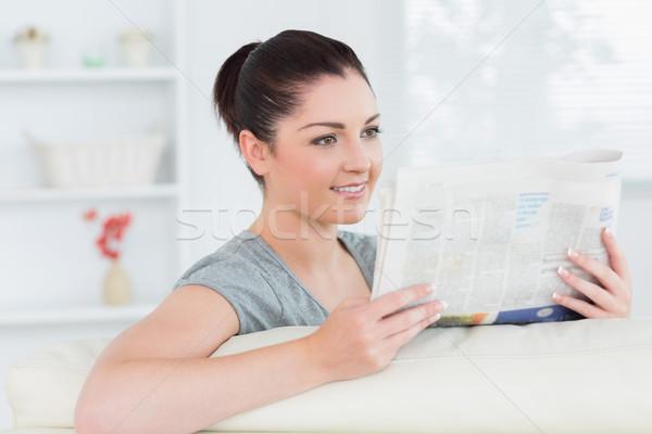 Uśmiechnięta kobieta posiedzenia au salon czytania gazety Zdjęcia stock © wavebreak_media