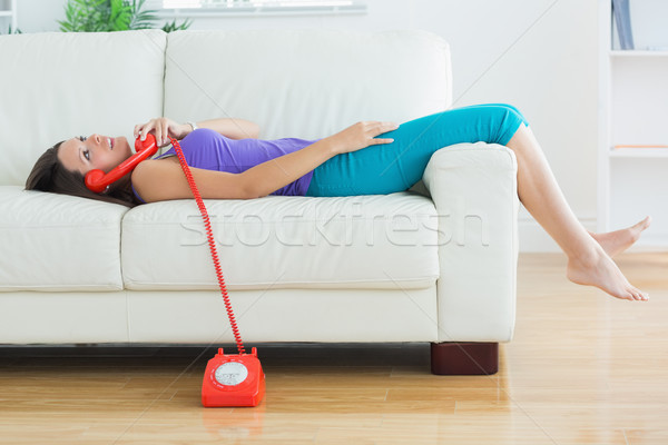 Happy woman lying on the sofa and phoning in the living room Stock photo © wavebreak_media