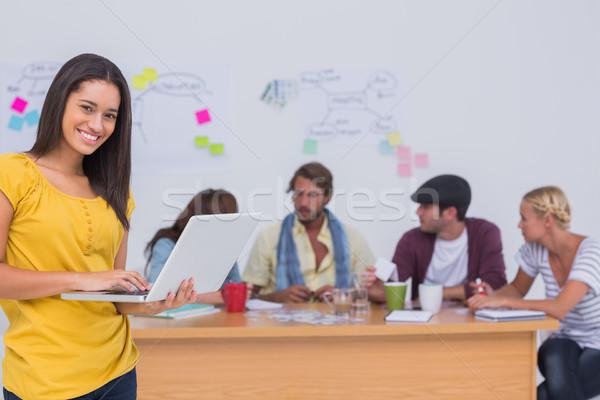 Editor usando laptop equipe atrás grande secretária Foto stock © wavebreak_media