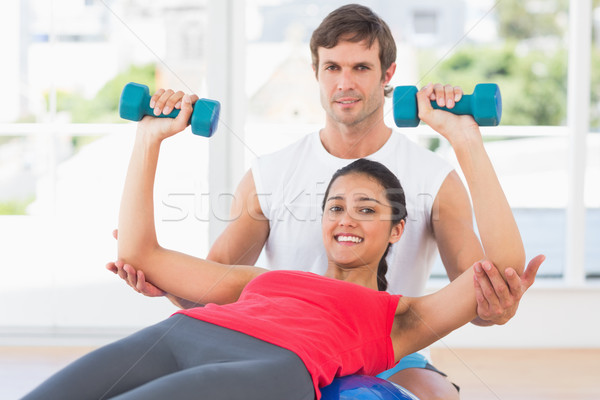 Smiling instructor with woman lifting dumbbell weights Stock photo © wavebreak_media