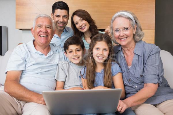 Extended family using laptop on sofa in living room Stock photo © wavebreak_media
