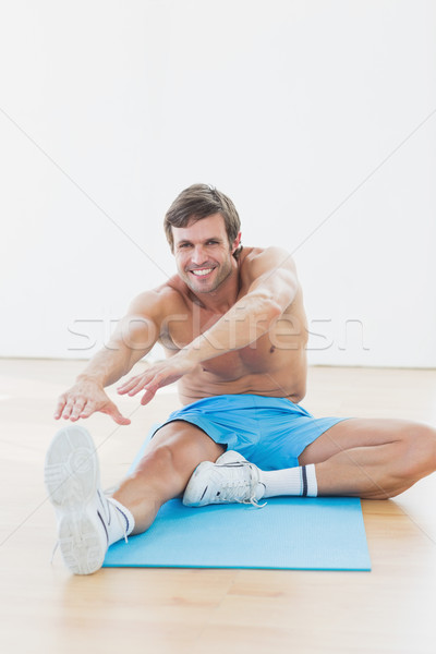 Sporty man stretching hands to leg in fitness studio Stock photo © wavebreak_media