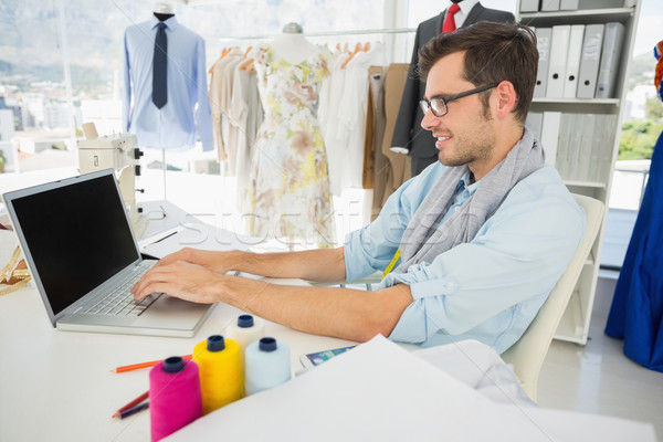 Concentrated young male fashion designer using laptop Stock photo © wavebreak_media
