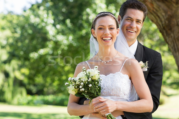 Newly wed couple with flower bouquet in park Stock photo © wavebreak_media