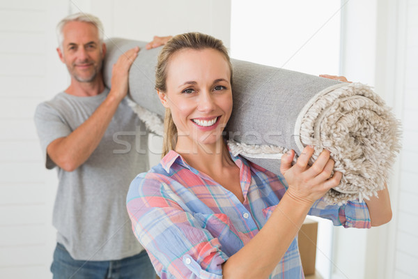 Happy couple carrying a rolled up rug together Stock photo © wavebreak_media