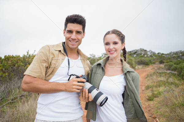 Hiking couple holding camera on mountain terrain Stock photo © wavebreak_media