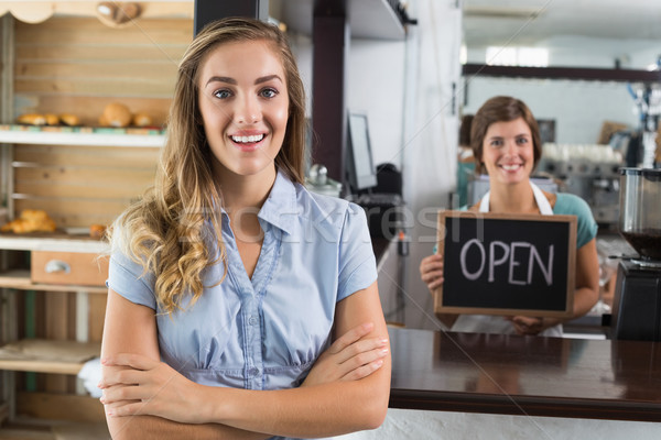 Pretty waitress and customer smiling at camera Stock photo © wavebreak_media