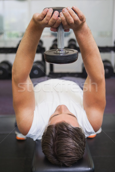 Fit man lifting dumbbell lying on the bench Stock photo © wavebreak_media