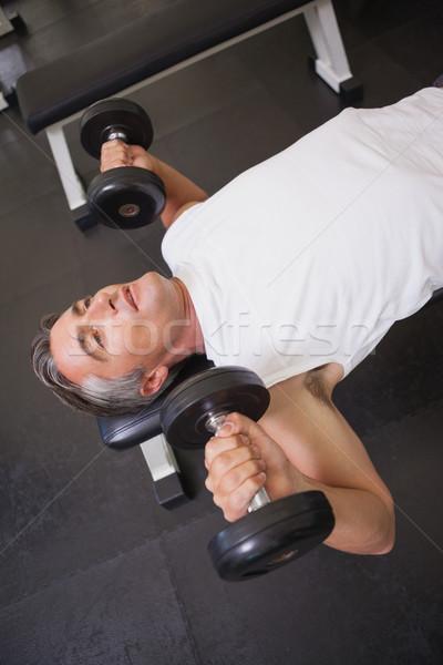 Fit man lifting dumbbells lying on the bench Stock photo © wavebreak_media