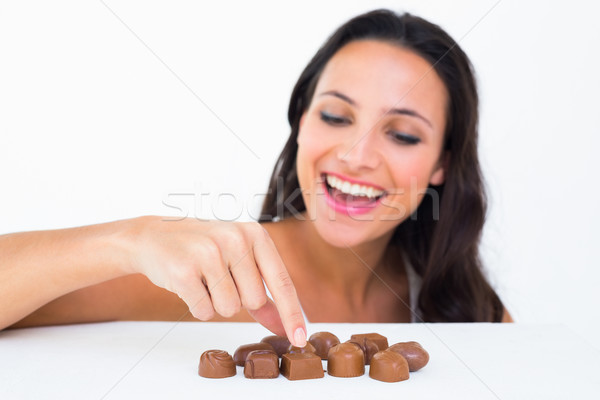 Pretty brunette picking out chocolate Stock photo © wavebreak_media